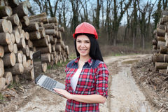 Female forest engineer beside logs Stock Image