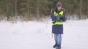 Female forester inspecting forest in winter