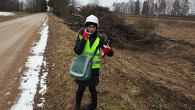Female forestry inspector talking on phone near pile of bushes. Near road stock video