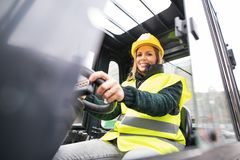 Woman forklift truck driver in an industrial area. Female forklift truck driver in an industrial area. A woman sitting in the fork lift outside a warehouse stock photos