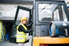 Female forklift truck driver outside a warehouse. A woman getting in the fork lift truck Stock Photo