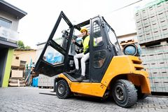 Female forklift truck driver outside a warehouse. A woman getting out of the fork lift truck Royalty Free Stock Photo