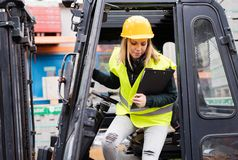 Female forklift truck driver outside a warehouse. A woman getting out of the fork lift truck, holding notes Royalty Free Stock Photography