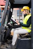 Female forklift truck driver outside a warehouse. A woman sitting in the fork lift making notes Royalty Free Stock Photos