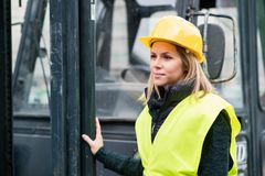 Female forklift truck driver outside a warehouse. A woman standing by the fork lift truck Royalty Free Stock Image
