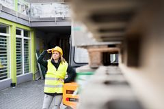 Female forklift truck driver outside a warehouse. A woman standing by the fork lift truck, looking at something Stock Photo