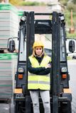 Female forklift truck driver outside a warehouse. A woman standing in front of the fork lift truck, arms crossed Stock Photography
