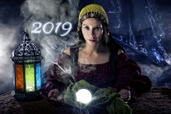 Fortune Teller Making Predictions for New Year 2019. Female fortune teller or psychic reading with a cystal ball predicting the future of the year 2019 stock images