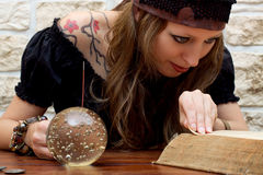 Female fortune teller suggests the future. Fortune teller reads a book and suggests the future Royalty Free Stock Photography