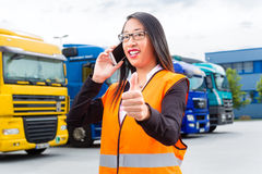 Female forwarder in front of trucks on a depot. Logistics - female Asian forwarder or supervisor with mobile phone, in front of trucks and trailers, on stock photography