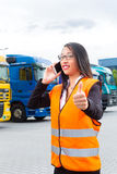 Female forwarder in front of trucks on a depot. Logistics - female Asian forwarder or supervisor with mobile phone, in front of trucks and trailers, on stock photos
