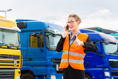 Female forwarder in front of trucks on a depot. Logistics - female forwarder or supervisor with mobile phone, in front of trucks and trailers, on transshipment royalty free stock images