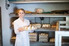 Female fowl-farm worker packing eggs stock image
