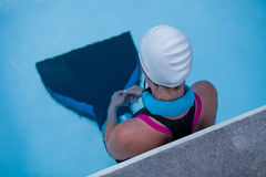 Female freediver at pool edge. Female freediver with monofin concentrating and preparing at edge swimming pool royalty free stock images