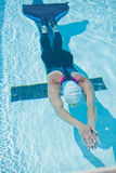 Female freediver in pool. Female freediver with monofin swimming underwater in swimming pool stock photo
