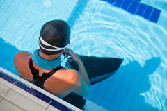 Female freediver at pool. Female freediver with neck weight and monofin at edge of outdoor swimming pool Royalty Free Stock Photos