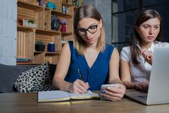 Two women using cell telephone and laptop computer for teamwork. Female freelance social media content manager writing information in diary from mobile phone Royalty Free Stock Photo