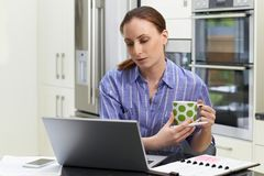 Female Freelance Worker Using Laptop And Drinking Coffee In Kitchen At Home. Female Freelance Worker Using Laptop And Drinking Coffee In Kitchen stock images