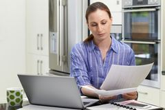 Female Freelance Worker Using Laptop In Kitchen At Home. Female Freelance Worker Uses Laptop In Kitchen At Home stock photography