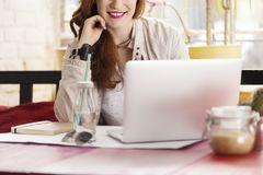Female freelancer in coffee shop. Smiling female freelancer searching the internet in trendy coffee shop Royalty Free Stock Images