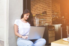 Female freelancer  connecting to cafe wireless for remote work via net-book Royalty Free Stock Photography