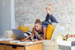 Female freelancer in her casual home clothing working remotly from her dining table in the morning. Houses on a sofa on. A white brick wall background royalty free stock image