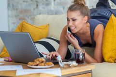 Female freelancer in her casual home clothing working remotly from her dining table in the morning. Houses on a sofa on Stock Photo