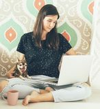 Female freelancer with laptop sitting on the floor. Young stylish woman freelancer with a laptop sits comfortably on the floor, holds a dog, next to a cup of royalty free stock photo