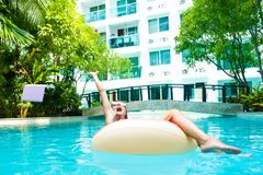 Female freelancer sits in an inflatable circle in the pool and throws the laptop into the water. Busy during the stock image