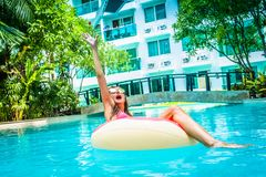 Female freelancer sits in an inflatable circle in the pool and throws the laptop into the water. Busy during the royalty free stock image