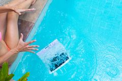 Female freelancer sits by the pool and works on a minicomputer, drops her laptop into the water. Busy during the royalty free stock image