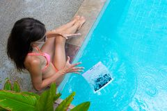 Female freelancer sits by the pool and works on a minicomputer, drops her laptop into the water. Busy during the royalty free stock photos