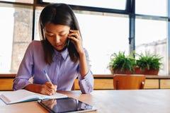 Female freelancer taking notes Stock Photo