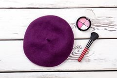 Female french beret and cosmetics. Women autumn hat, eyeshadows and brush on white wooden background. Ladies bright accessories stock photo