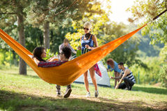 Female friend brings beer to couple in love in hammock Royalty Free Stock Photography