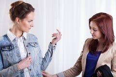 Female friend trying on denim jacket Stock Photos