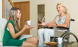 Female friend visiting disabled woman. Female friend visiting positive disabled women on chair indoor Stock Photo