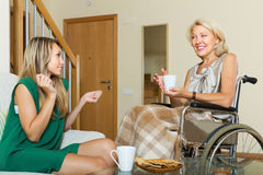Female friend visiting disabled woman Stock Photos