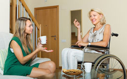 Female friend visiting disabled woman Royalty Free Stock Photos