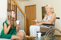 Female friend visiting disabled woman Royalty Free Stock Image