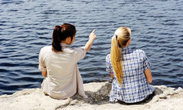 Female friends. Friends sit next to a lake and point at the view stock images