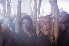 Female friends with arms raised enjoying at nightclub Stock Photo