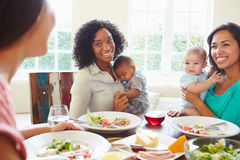 Female Friends With Babies Enjoying Meal At Home Together stock photo