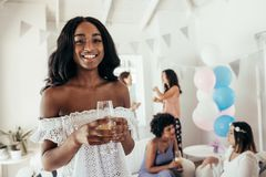 Female friends at baby shower party. Smiling african young women holding a glass of juice with friends in background at baby shower party. Female friends at baby stock image