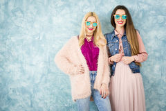 Female friends on the blue wall background Royalty Free Stock Images