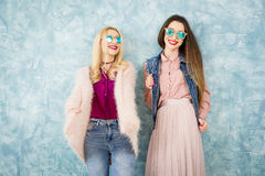 Female friends on the blue wall background Royalty Free Stock Photography