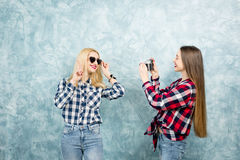 Female friends on the blue wall background Stock Photos