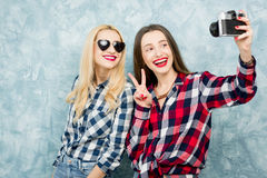 Female friends on the blue wall background Royalty Free Stock Image