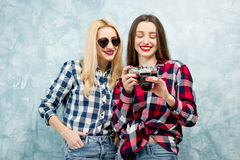 Female friends on the blue wall background Royalty Free Stock Photos