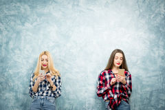 Female friends on the blue wall background Stock Photography